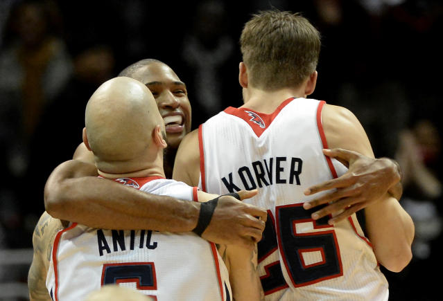 Atlanta Hawks center Al Horford, center, celebrates the win with teammates Pero Antic, left, and Kyle Korver after he hits a jumper at the buzzer in overtime to score over Washington Wizards' Trevor Booker in an NBA basketball game on Friday, Dec. 13, 2013, in Atlanta. Atlanta won 101-99. (AP Photo/David Tulis)