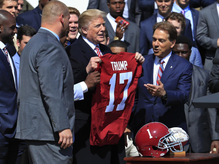 President Donald Trump holds up a team jersey presented to him by Alabama coach Nick Saban after the Tide's national championship win over Georgia in 2018. (AP/Manuel Balce Ceneta)