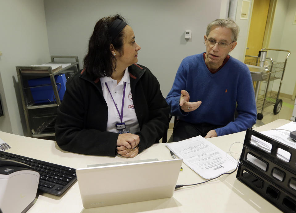 Chris Rogers, right, talks to Epilepsy Foundation Navigator Barbara Meneses as Rogers prepares to enroll for health care coverage, Tuesday, Jan. 12, 2016, in Coral Gables, Fla. Thousands of health insurance consumers around the country have started the new year dealing with missing ID cards, billing errors and other problems tied to an enrollment surge at the end of 2015. Brokers and insurers in several states told The Associated Press that they've been inundated with complaints about these issues from customers with individual plans and those with coverage through small businesses. (AP Photo/Alan Diaz)