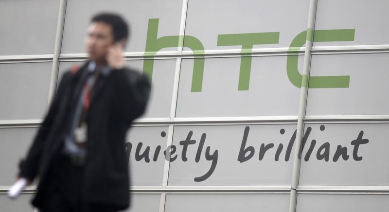 Visitors walk past a HTC sign at the GSMA Mobile World Congress in Barcelona