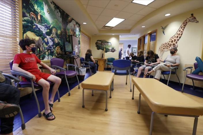 Aidan Mohl, 13, joins others in a waiting room after receiving Pfizer's vaccine against coronavirus disease (COVID-19), after Georgia authorized the vaccine for ages over 12 years, at Dekalb Pediatric Center in Decatur
