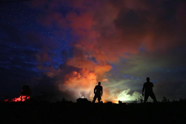 <p>Photographers work as lava from active fissures illuminates volcanic gases from the Kilauea volcano on Hawaii's Big Island on May 15, 2018 in Hawaii Volcanoes National Park, Hawaii. (Photo: Mario Tama/Getty Images) </p>