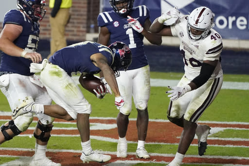 Mississippi running back Jerrion Ealy (9) follows his blockers as he rushes for a 8-yard touchdown as Mississippi State linebacker Erroll Thompson (40) comes up to defend during the second half of an NCAA college football game against Mississippi State, Saturday, Nov. 28, 2020, in Oxford, Miss. (AP Photo/Rogelio V. Solis)