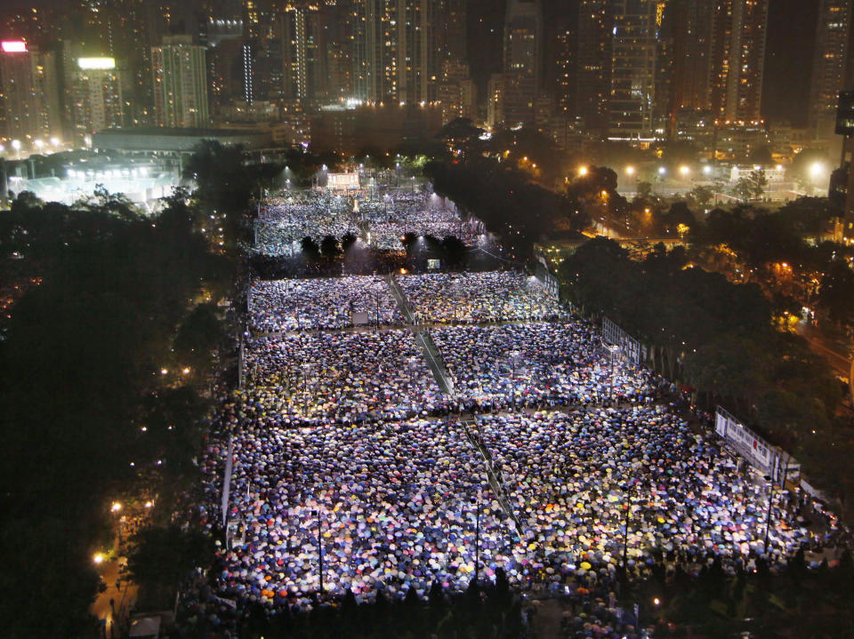FILE - In this June 4, 2013, file photo, thousands of people attend a candlelight vigil in Hong Kong's Victoria Park to mark the anniversary of the military crackdown on a pro-democracy student movement in Beijing. (AP Photo/Kin Cheung, File)
