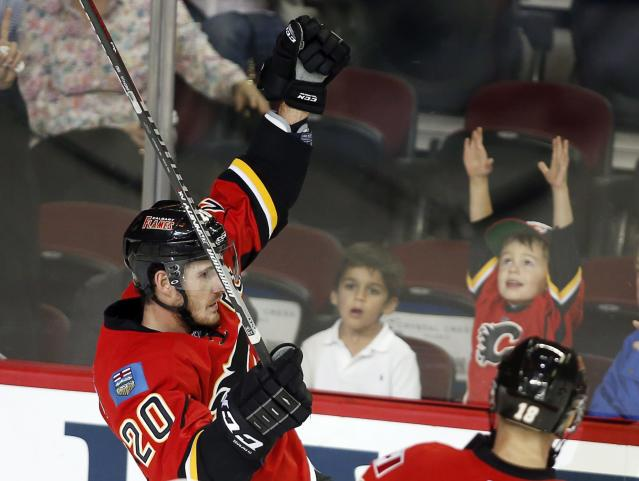 Calgary Flames' Curtis Glencross, left, celebrates his goal, in front of a young fan, during the first period of an NHL hockey preseason game against the New York Rangers on Monday, Sept. 23, 2013, in Calgary, Alberta. (AP Photo/The Canadian Press, Jeff McIntosh)