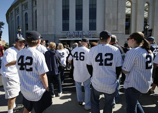 Fans of New York Yankees relief pitcher Mariano Rivera, (42) and starting pitcher Andy Pettitte (46) line up outside Yankee Stadium before a baseball game against the San Francisco Giants, Sunday, Sept. 22, 2013, in New York. Pettitte, the winningest active pitcher, is scheduled to pitch what is likely to be his last game as relief pitcher Mariano Rivera, will be honored in a retirement ceremony. (AP Photo/Kathy Willens)
