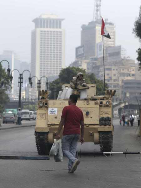 "An Egyptian walks in front of an army armored vehicle that guards an entrance of Tahrir Square, in Cairo, Egypt, Friday, Aug. 16, 2013. Egypt is bracing for more violence after the Muslim Brotherhood called for nationwide marches after Friday prayers and a ""day of rage"" to denounce this week's unprecedented bloodshed in the security forces' assault on the supporters of the country's ousted Islamist president that left more many hundreds dead. (AP Photo/Hassan Ammar)"