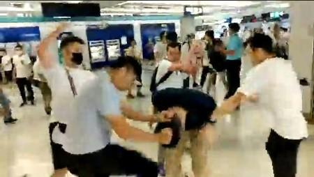 Social media video grab of men in white t-shirts and face masks attacking anti-extradition bill demonstrators and reporters at a train station in Hong Kong