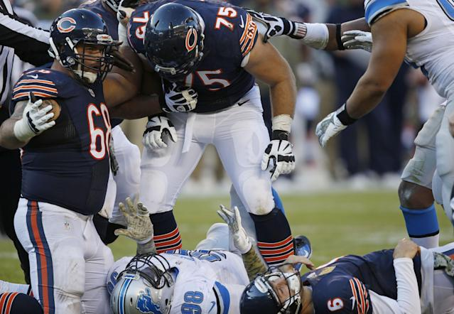 Chicago Bears offensive guard Kyle Long (75) yells down at Detroit Lions defensive tackle Nick Fairley (98) as Bears quarterback Jay Cutler (6) lays on the ground after a play during the second half of an NFL football game, Sunday, Nov. 10, 2013, in Chicago. (AP Photo/Charles Rex Arbogast)