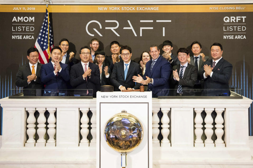 In this photo provided by the New York Stock Exchange, Hyungsik Kim, center, founder and Chief Executive Officer of Qraft Technologies of Seoul, South Korea, and guests, join Douglas Yones, foreground, third from right, on the podium for the closing bell at the New York Stock Exchange, Thursday, June 11, 2019 in New York. The Dow Jones Industrial Average climbed above 27,000 for the first time after a turbulent day on Wall Street, closing at 27,088.08. (Courtney Crow/The New York Stock Exchange via AP)