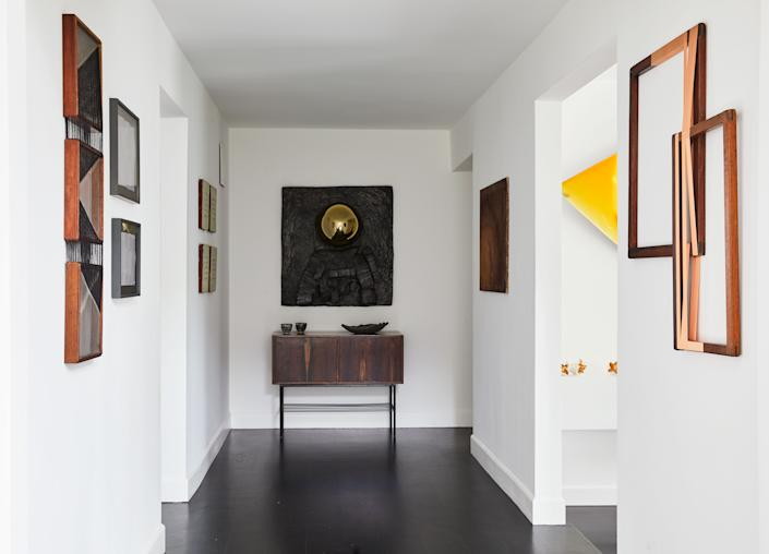 "<div class=""caption""> In this hallway, a Geraldo de Barros jacarandá sideboard is a perfect match for Brazilian artist Erika Verzutti's bronze-and-glass wall sculpture. The side walls are hung with works by Paloma Bosquê, also from Brazil, Mona Hatoum, a Palestinian multimedia artist, the American multidisciplinary artist Michelle Stuart, and Sergej Jensen, a Danish painter. </div>"