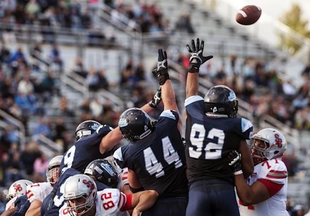 Maine defensive players Michael Cole (9), Patrick Rickard (44) and Trevor Bates (92) attempt a block a Stony Brook field goal in the second half of an NCAA college football game in Orono, Maine, Saturday, Nov. 2, 2013. (AP Photo/Michael C. York)