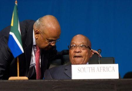 South Africa's Finance Minister Pravin Gordhan speaks to President Jacob Zuma during closing remarks during the 5th BRICS Summit in Durban