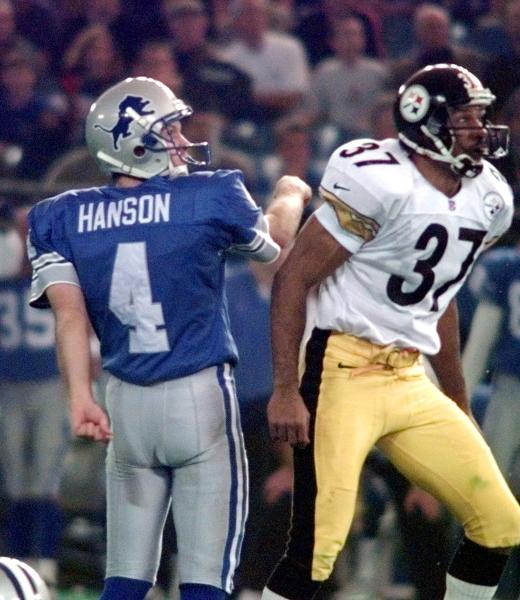 """FILE - In this Thursday, Nov. 26, 1998, file photo, Detroit Lions kicker Jason Hanson (4) watches his game-winning field goal in overtime with Pittsburgh Steelers cornerback Carnell Lake (37) during an NFL football game at the Silverdome in Pontiac, Mich. After a Lions rally to send game in to overtime, the coin toss was held to determine possession. Steelers Jerome Bettis begins to call """"heads"""" and then switches to """"tails"""" as the toss comes up """"tails."""" But the Lions are awarded ball since rule says first call stands. Hanson hits the winning field goal on the Lions' first possession for a 19-16 win. (AP Photo/Carlos Osorio, File)"""