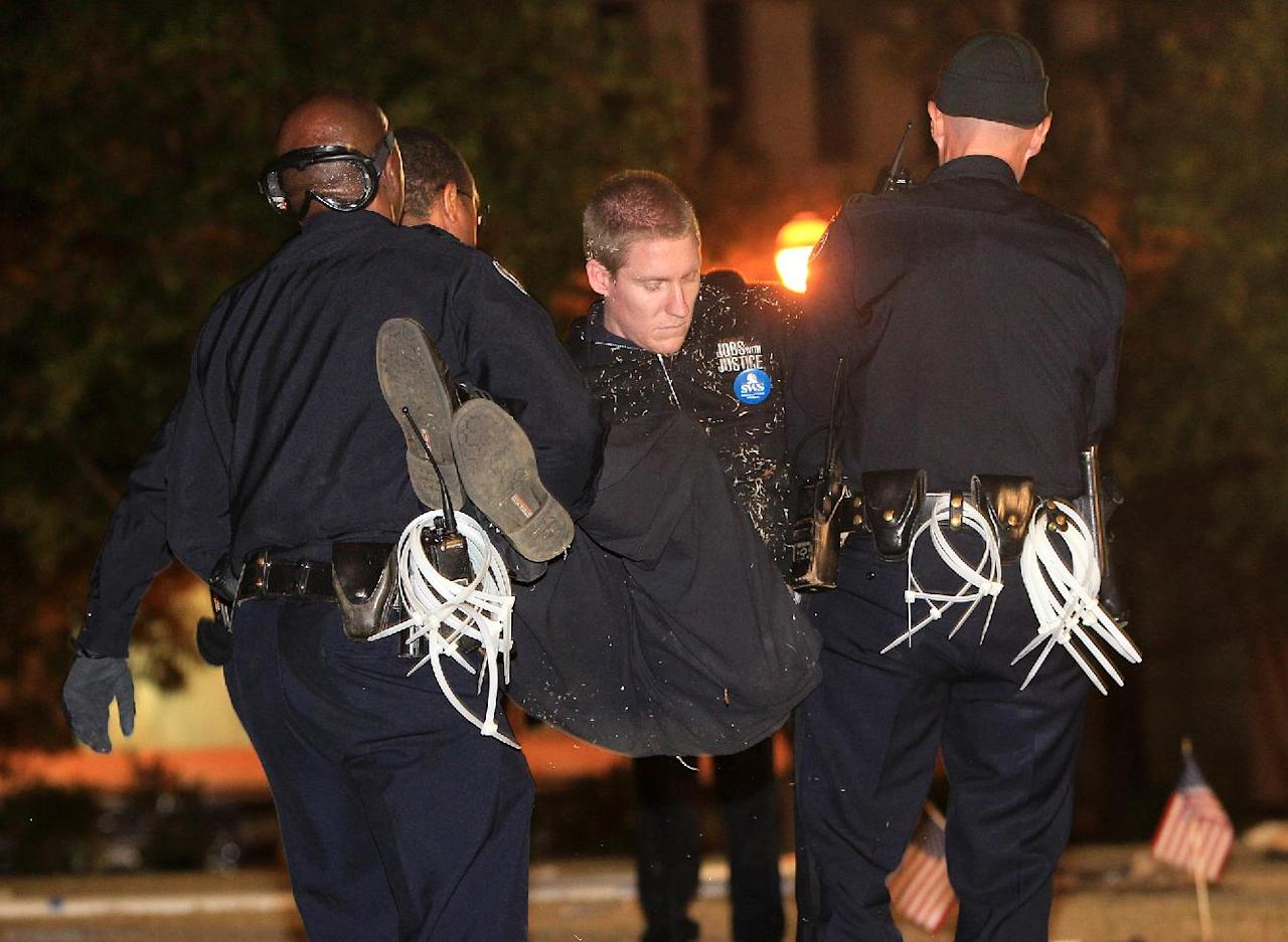 Atlanta police carry away one of dozens of Occupy Atlanta protesters arrested at Woodruff Park early Wednesday morning, Oct. 26, 2011, in Atlanta. Before police moved in, protesters were warned a couple times around midnight to vacate the park or risk arrest. (AP Photo/Curtis Compton?Atlanta Journal Constitution)