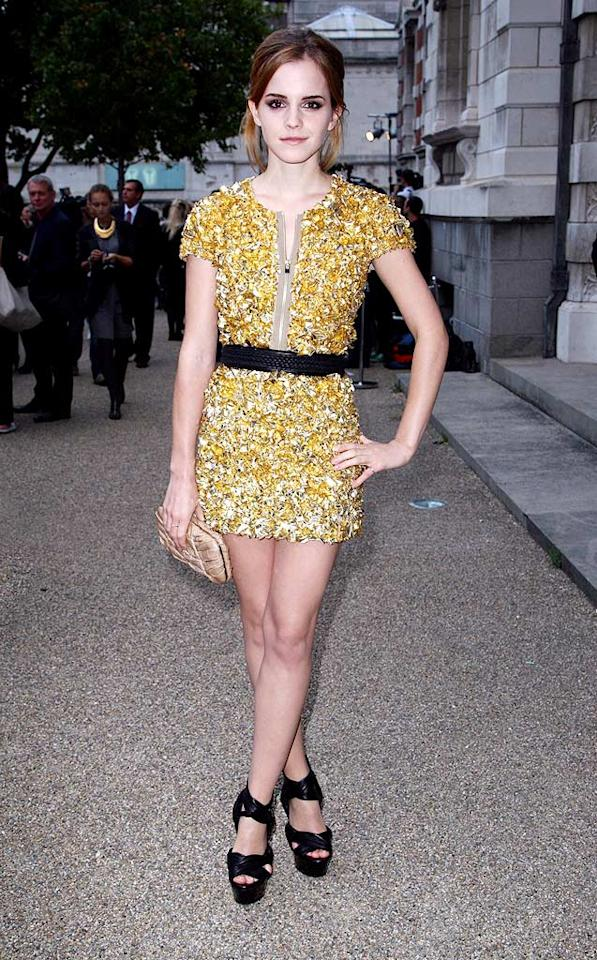 "Across the pond in London, Burberry poster girl Emma Watson wowed the crowd as she arrived at the design house's spring/summer 2010 fashion show in a gold foil mini, black braided belt, and matching platform heels. Dave Hogan/Mission Pictures/<a href=""http://www.gettyimages.com/"" target=""new"">GettyImages.com</a> - September 22, 2009"