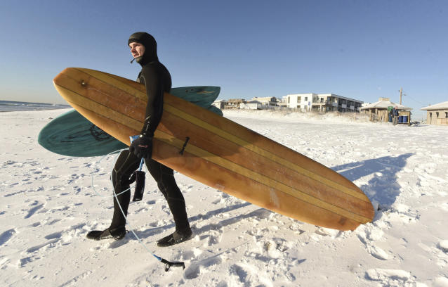 <p>Kevin Cagle heads out to surf along Wrightsville Beach, N.C. Thursday Jan. 4, 2017. (Photo: Ken Blevins/The Wilmington News-Journal via AP) </p>