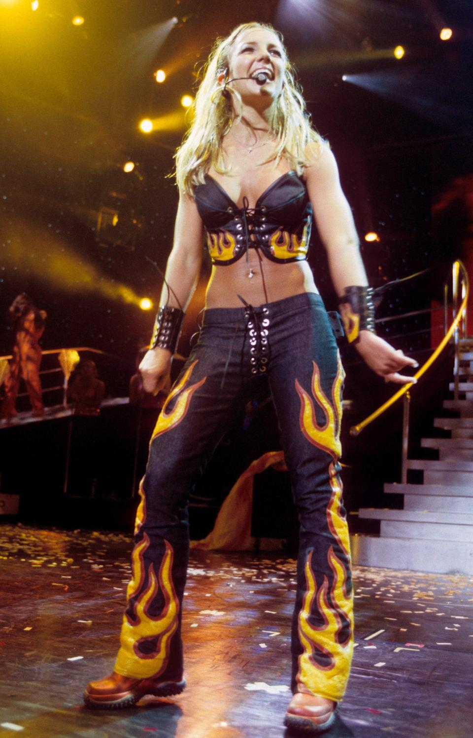 <p>Wearing a flame-print crop top and pants while performing on stage.</p>