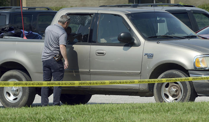 An investigator looks through the broken windows of a truck in the parking lot near the Regional Hospital ambulance entrance on Wednesday, July 7 2021 in Terre Haute, Ind. A suspected gunman in the fatal ambush shooting of Terre Haute Police Det. Greg Ferency left the scene and drove himself to the hospital, where he underwent surgery for his wounds, said Paul Keenan, the special agent in charge of the FBI's Indianapolis office. (Joseph C. Garza/The Tribune-Star via AP)