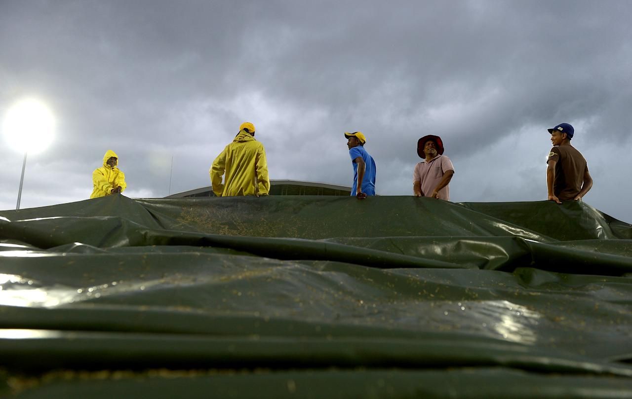 Sri Lankan groundstaff use a tarpaulin to cover the ground as rain stops play during the second One Day International (ODI) cricket match between Sri Lanka and New Zealand at the Suriyawewa Mahinda Rajapakse International Cricket Stadium in the southern district of Hambantota on November 12, 2013. AFP PHOTO/ LAKRUWAN WANNIARACHCHI        (Photo credit should read LAKRUWAN WANNIARACHCHI/AFP/Getty Images)