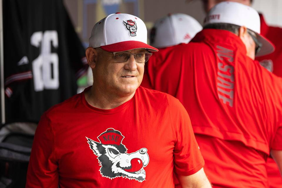 North Carolina State head coach Elliott Avent talks with others in the dugout during a COVID-19 protocol delay before playing against Vanderbilt during a baseball game in the College World Series, Friday, June 25, 2021, at TD Ameritrade Park in Omaha, Neb. (AP Photo/Rebecca S. Gratz)
