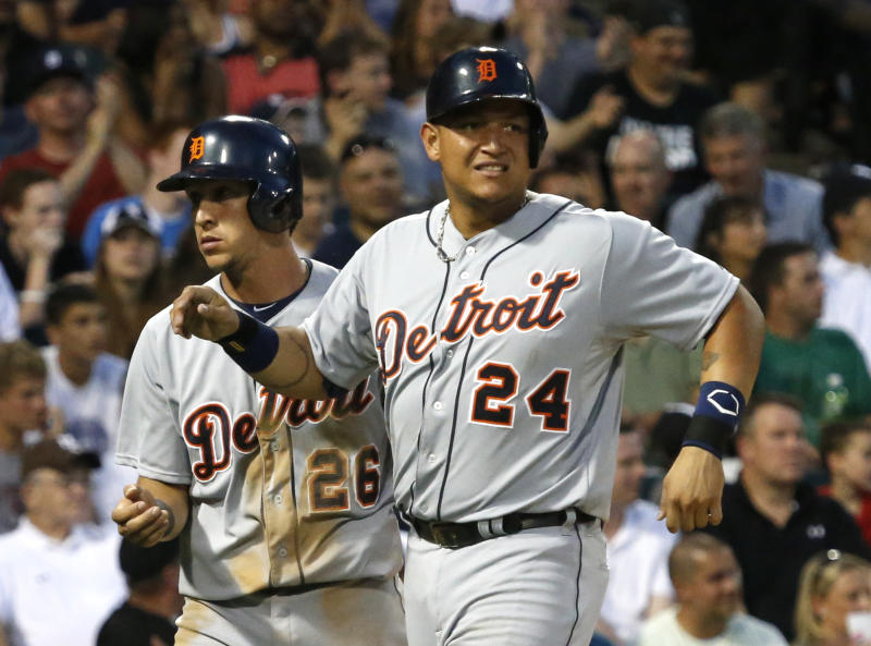 Detroit Tigers' Miguel Cabrera, right, grimaces after scoring with Hernan Perez, left, on a single by Victor Martinez, off a pitch by Chicago White Sox starting pitcher Chris Sale, during the fifth inning of a baseball game Monday, July 22, 2013, in Chicago. Cabrera left the game in the bottom of the fifth. (AP Photo/Charles Rex Arbogast)