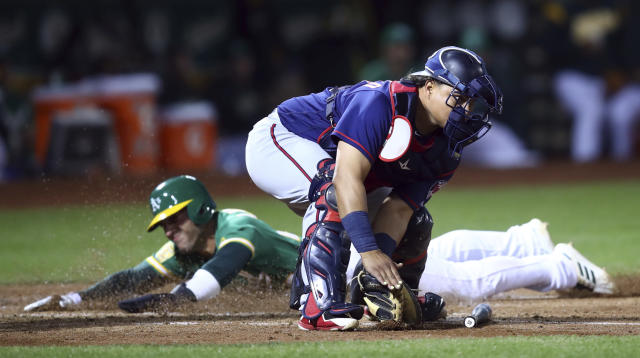 Oakland Athletics' Ramon Laureano scores behind Minnesota Twins catcher Willians Astudillo during the second inning of a baseball game Friday, Sept. 21, 2018, in Oakland, Calif. (AP Photo/Ben Margot)