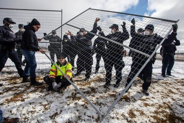 Supporters try to tear down the fence as police struggle with them outside GraceLife Church near Edmonton on Sunday, April 11. The church had been fenced off by police and Alberta Health Services in violation of COVID-19 rules.