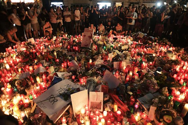 <p>AUG. 18, 2017 – People stand next to flowers, candles and other items set up on the Las Ramblas boulevard in Barcelona as they pay tribute to the victims of the Barcelona attack.<br> Drivers, on August 17, 2017 plowed into pedestrians in two quick-succession, separate attacks in Barcelona and another popular Spanish seaside city, leaving 14 people dead and injuring more than 100 others. Some eight hours later in Cambrils, a city 120 kilometres south of Barcelona, an Audi A3 car rammed into pedestrians, injuring six civilians and a police officer. (Photo: Javier Soriano/AFP/Getty Images) </p>