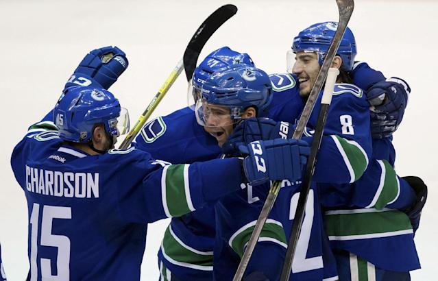 Vancouver Canucks' Brad Richardson, from left to right, Dan Hamhuis, David Booth and Chris Tanev celebrate Tanev's goal against the Winnipeg Jets during the third period of an NHL hockey game in Vancouver, British Columbia, on Sunday, Dec. 22, 2013. (AP Photo/The Canadian Press, Darryl Dyck)