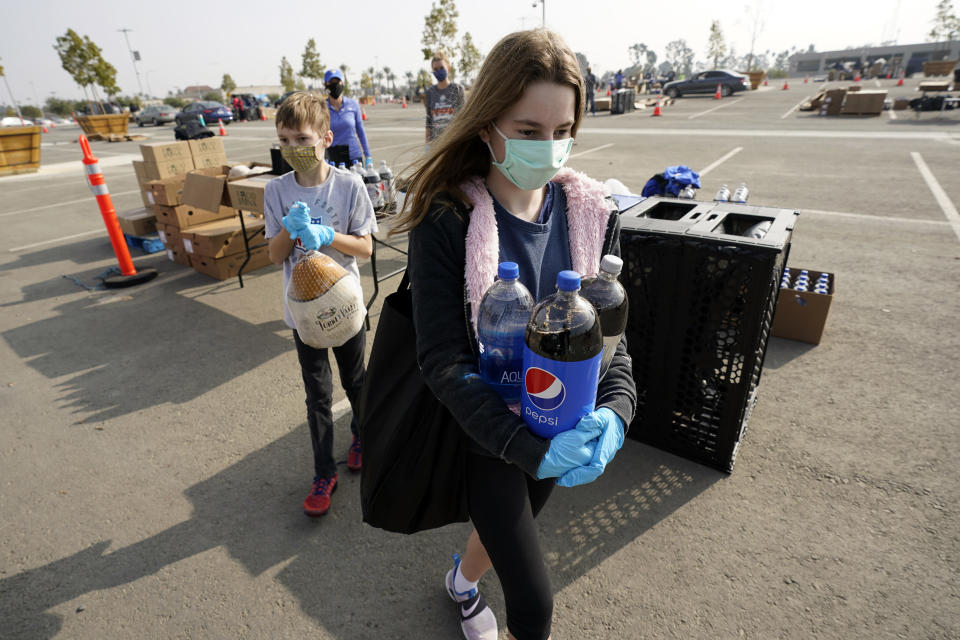Claire Demoff, 13, foreground, and her brother Owen, 11, volunteer at a food distribution center set up at SoFi Stadium amid the COVID-19 pandemic and ahead of Thanksgiving, Monday, Nov. 23, 2020, in Inglewood, Calif. (AP Photo/Marcio Jose Sanchez)