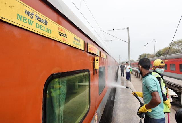 Railway cleaning staff chemically disinfect and sanitize a Rajdhani train as a precautionary measure in view of coronavirus concerns in New Delhi.