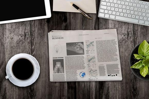 A newspaper next to a tablet and a cup of coffee