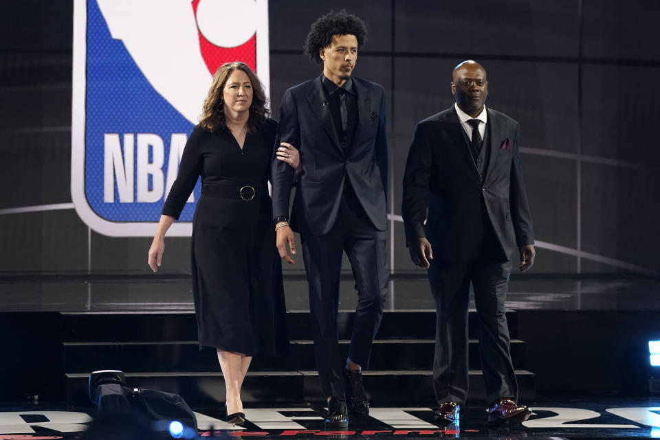 Cade Cunningham, center, walks with his parents, Carrie, left, and Keith Cunningham during the NBA basketball draft, Thursday, July 29, 2021, in New York. Cunningham was selected first overall by the Detroit Pistons. - Credit: AP