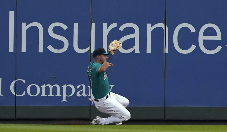 Seattle Mariners right fielder Jake Bauers makes a sliding catch of a fly ball hit by Los Angeles Angels' Taylor Ward to end the top of the sixth inning, stranding two runners, Friday, July 9, 2021, in Seattle. (AP Photo/Ted S. Warren)