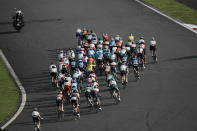 The peloton makes a turn during the men's cycling road race at the 2020 Summer Olympics, Saturday, July 24, 2021, in Oyama, Japan. (AP Photo/Thibault Camus)