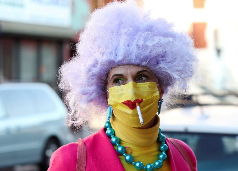 FILE PHOTO: A woman dressed up for Halloween as a Simpsons character smokes a cigarette through a protective mask in Brooklyn