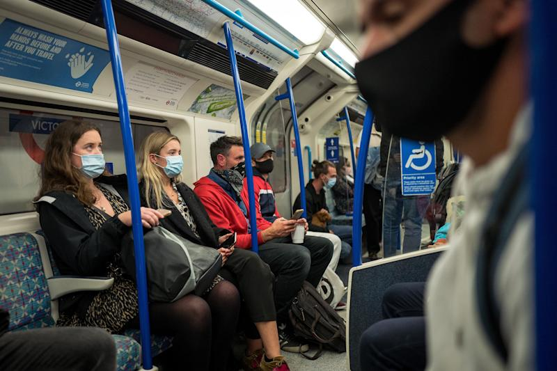 Commuters wearing face masks or covering due to the COVID-19 pandemic, sit aboard a Victoria Line London underground tube train as they travel during the evening 'rush hour' in central London on September 23, 2020. - The UK on Wednesday reported 6,178 new coronavirus cases, a marked jump in the daily infection rate that comes a day after Prime Minister Boris Johnson unveiled new nationwide restrictions. (Photo by Tolga AKMEN / AFP) (Photo by TOLGA AKMEN/AFP via Getty Images)