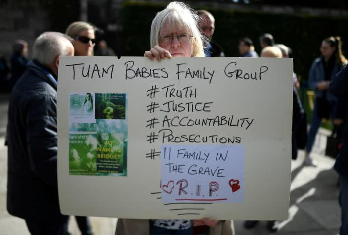 FILE PHOTO: A woman holds a poster at a funeral procession in remembrance of the bodies of the infants discovered in a septic tank, in 2014, at the Tuam Mother and Baby Home, in Dublin
