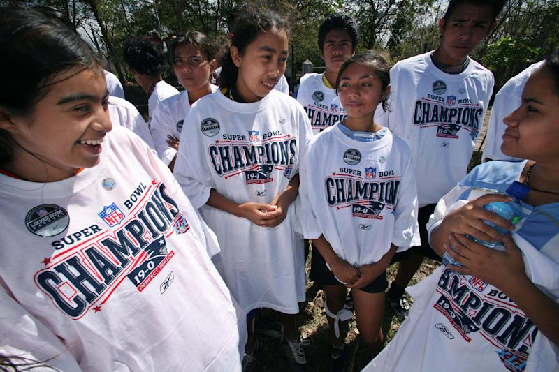 "Members of Buena Vista soccer team wear donated T-shirts hailing the New England Patriots as ""Super Bowl Champions, 19-0'' in San Gregorio, south of Managua, Thursday, Feb. 14, 2008. The NFL donated to impoverished children hats and clothing that had been prepared in advance in case the Patriots had won, but the Patriots lost the Feb. 3 game to the New York Giants 17-14. (AP Photo)"