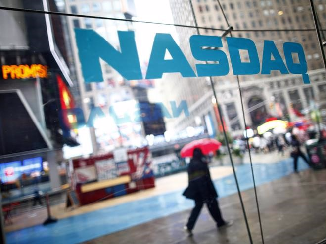 Pedestrians walk past the NASDAQ MarketSite in New York's Times Square in this June 4, 2012 file photo. REUTERS/Eric Thayer/Files