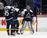 Colorado Avalanche left wing Andre Burakovsky, front, joins Colorado Avalanche defenseman Erik Johnson, center, in congratulating goaltender Pavel Francouz at the end of the team's NHL hockey game against the Nashville Predators on Thursday, Nov. 7, 2019, in Denver. Colorado won 9-4. (AP Photo/David Zalubowski)