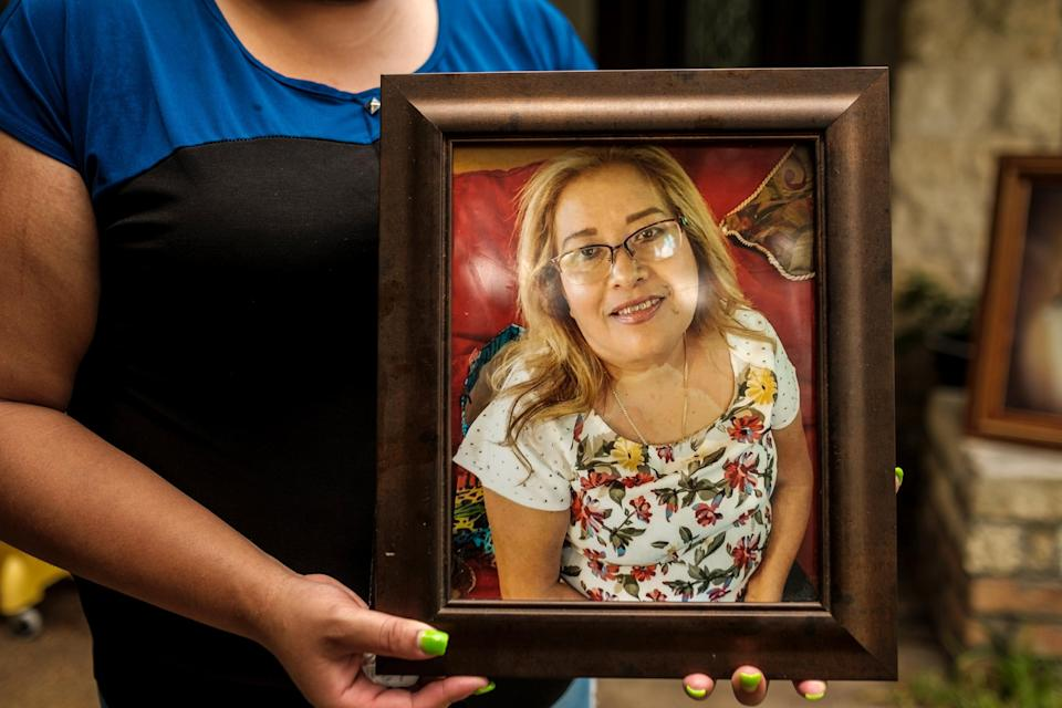 Image: Karen Salazar holds a picture of her mother, Felipa Medell?n, outside of her mother's home in Houston on July 7, 2020. (Fred Agho / for NBC News)