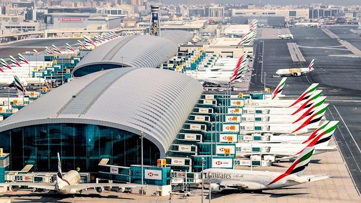 Lots of Emirates planes parked at a Dubai airport terminal
