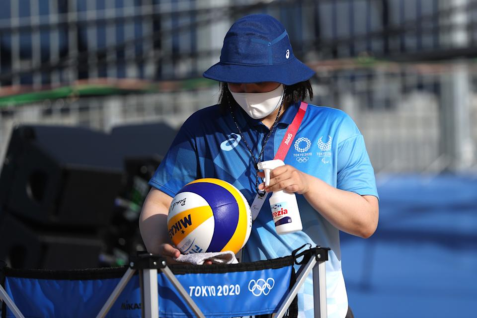 <p>A worker sanitizes beach volleyballs during training at Shiokaze Park ahead of the Tokyo 2020 Olympic Games on July 20, 2021 in Tokyo, Japan. (Photo by Sean M. Haffey/Getty Images)</p>