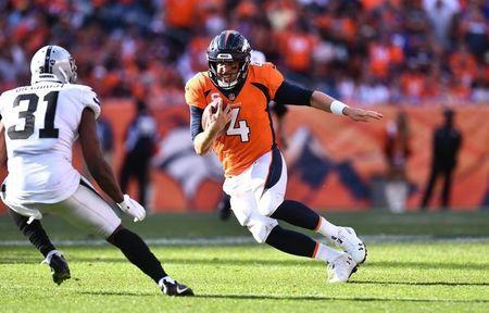 Sep 16, 2018; Denver, CO, USA; Denver Broncos quarterback Case Keenum (4) carries the football towards Oakland Raiders defensive back Marcus Gilchrist (31) in the fourth quarter at Broncos Stadium at Mile High. Mandatory Credit: Ron Chenoy-USA TODAY Sports