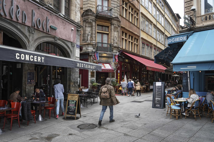 A man walks by restaurants in Lyon, central France, Tuesday, July 13, 2021. Nearly 1 million people in France made vaccine appointments in a single day, as the president cranked up pressure on everyone to get vaccinated to save summer vacation and the French economy. (AP Photo/Laurent Cipriani)