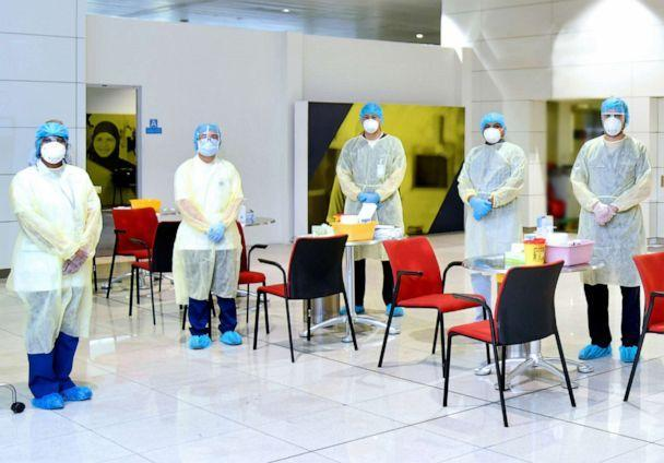 medical staff dressed in PPI in the airport around tables and chair to test passengers for COVID