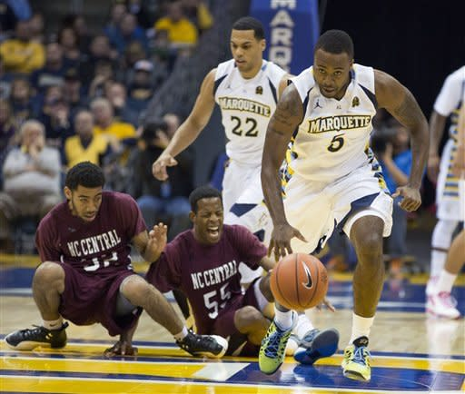 Marquette's Junior Cadougan makes a steal leaving North Carolina Centrals' Ray Willis, center, and teammate Emmanuel Chapman on the floor during the first half of an NCAA college basketball game, Saturday, Dec. 29, 2012, in Milwaukee. (AP Photo/Tom Lynn)