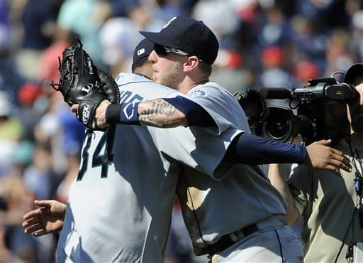 Seattle Mariners left fielder Mike Carp congratulates starting pitcher Felix Hernandez after the Mariners beat the Yankees 1-0 in a baseball game Saturday, Aug. 4, 2012, at Yankee Stadium in New York. Carp hit an RBI single in the game. (AP Photo/Kathy Kmonicek)